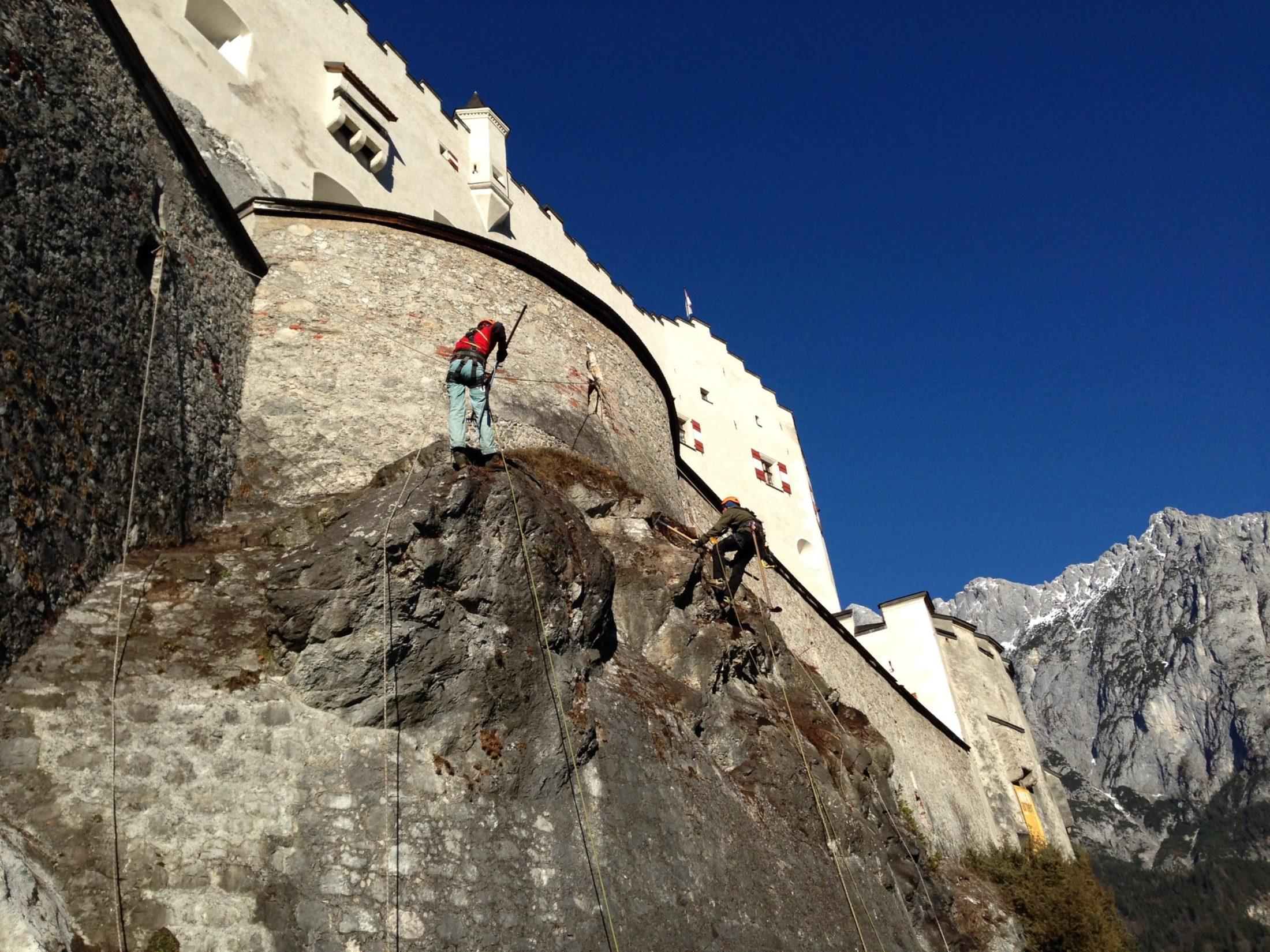 Zwei Männer seilen sich von der Burg Hohenwerfen ab und entferne loses Gestein