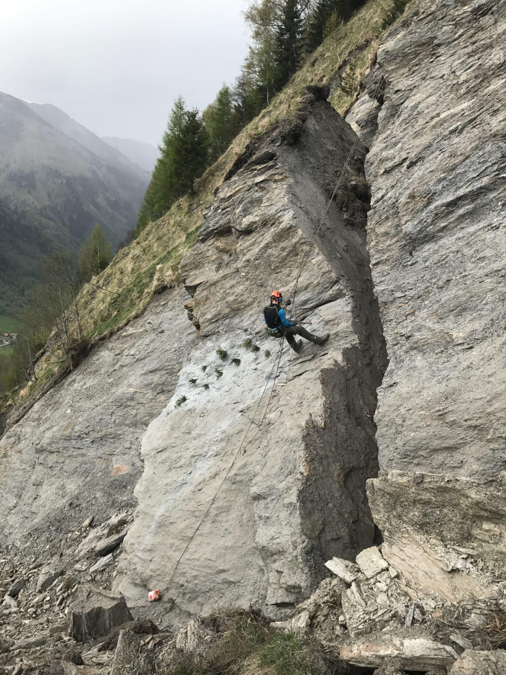 Ein Mann hängt mit einem Seil gesichert inmitten eines großen Felsen