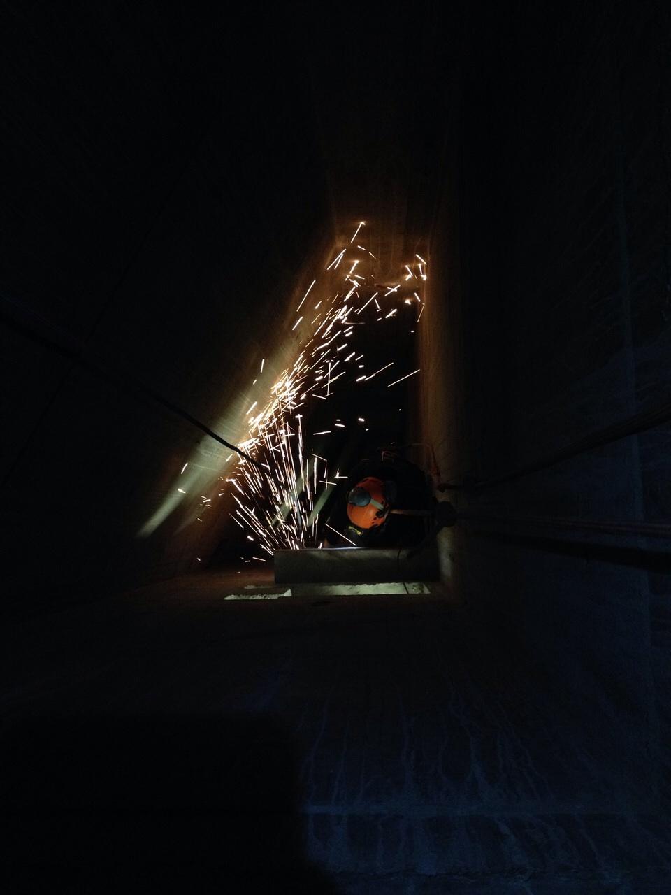 Arbeit mit der Flex in einem dunklen Schacht