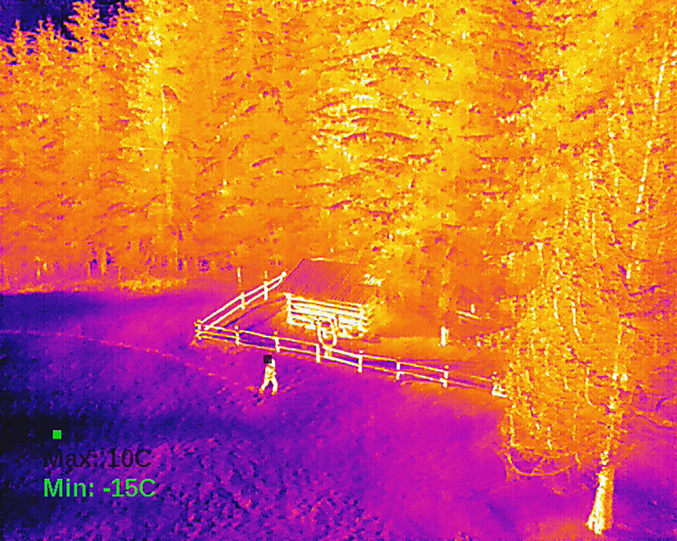 Infrarotaufnahme - Mann vor einer Hütte am Waldrand