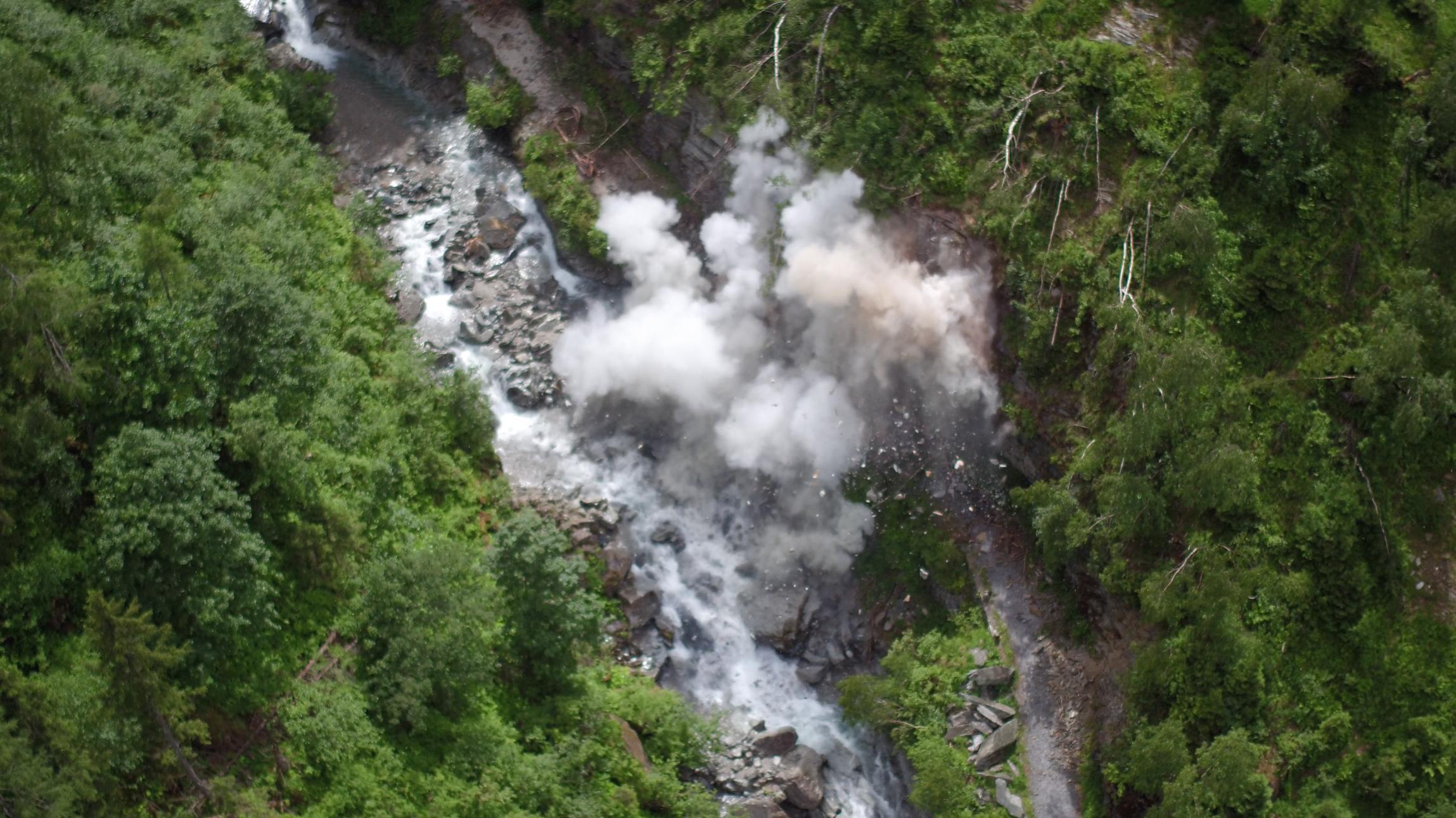 Staubwolke einer Sprengung direkt über einem Wildbach